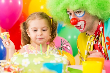 birthday clown: happy child girl with clown on birthday party