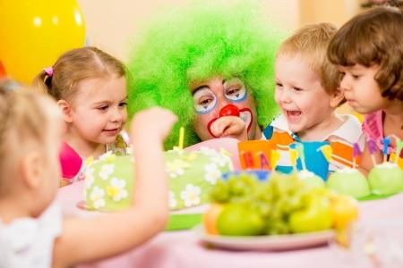 kids celebrating birthday party with clown photo