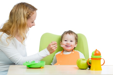 porridge: young mother spoon feeding her baby boy isolated on white Stock Photo