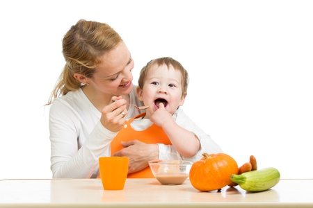 baby eating: young mother spoon feeding her baby boy isolated on white Stock Photo