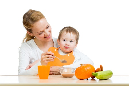 young mother spoon feeding her baby boy isolated on white photo
