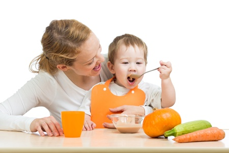 children eating: baby eating vegetables puree by spoon and sitting on mother laps Stock Photo
