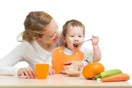 ni�os comiendo: beb� comiendo pur� de verduras con una cuchara y se sienta en el regazo de la madre