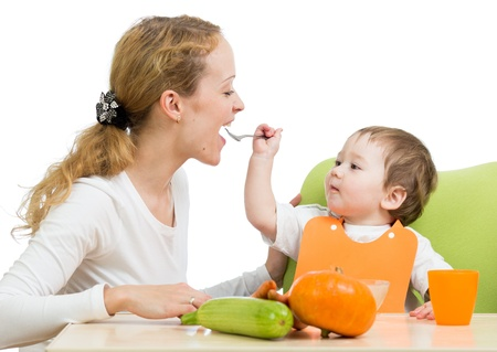 kids eating healthy: playful baby spoon feeding his mother isolated on white