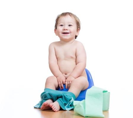 vasino: bambino ragazzo sorridente seduto sul vaso da notte con rotolo carta igienica