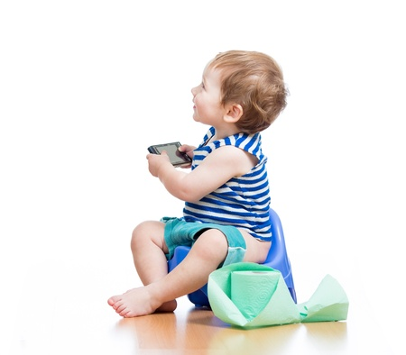 funny baby sitting on chamber pot with pda and toilet paper roll photo
