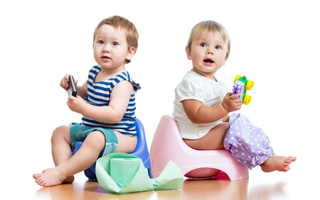 potty training: babies toddlers sitting on chamber pot and playing with toys