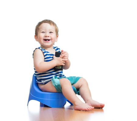 potty training: funny baby sitting on chamber pot and listening pda