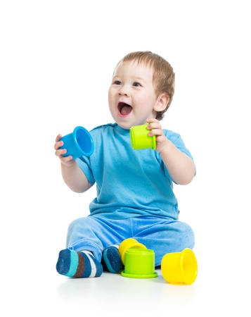 baby playing with colourful cup toys on floor, isolated over white photo