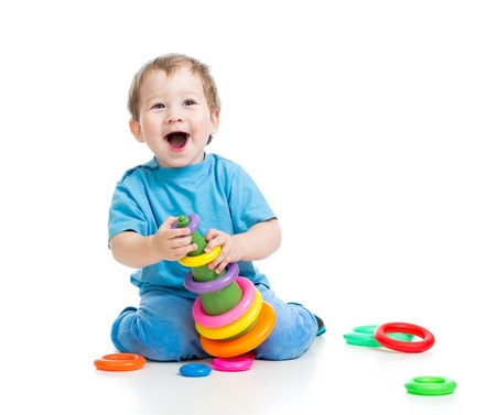 baby playing: cheerful little girl playing with colorful toy isolated on white
