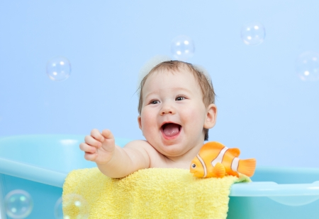 adorable child boy taking bath in blue tub photo