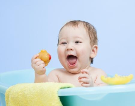 adorable child boy taking bath in blue tub photo