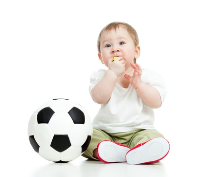 football shoes: adorable baby football player with ball and whistle over white background Stock Photo