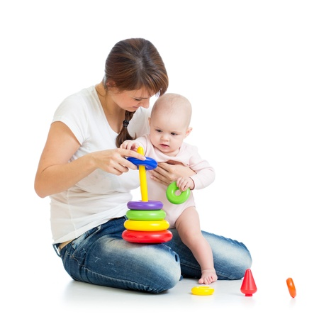 baby girl and mother playing together with construction set toy photo