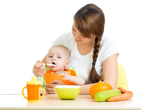 a little dinner: young mother spoon feeding her baby isolated on white Stock Photo