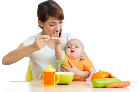 porridge: young mother spoon feeding her baby isolated on white Stock Photo