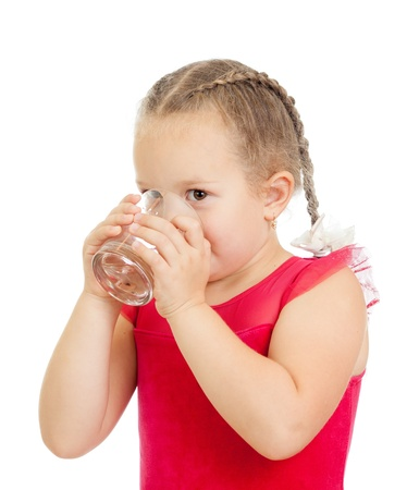 little girl drinking water from glass over white background photo
