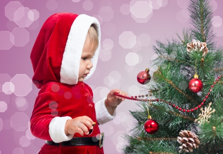 pretty Santa Claus baby decorating Christmas tree on bright festive background photo