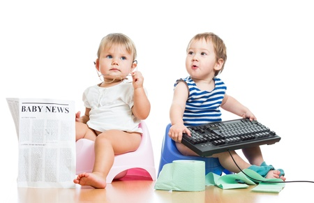 baby wardrobe: funny children girl and boy sitting on chamberpot with newspaper and keyboard Stock Photo