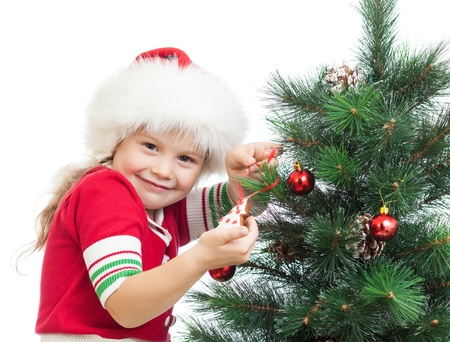 happy preschool girl decorating Christmas tree isolated on white photo