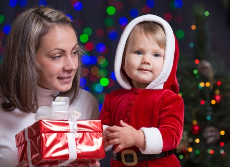 baby girl and her mother holding giftbox on bright festive background Stock Photo - 15763810