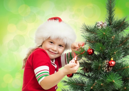 happy preschool girl decorating Christmas tree on green blurwhite photo