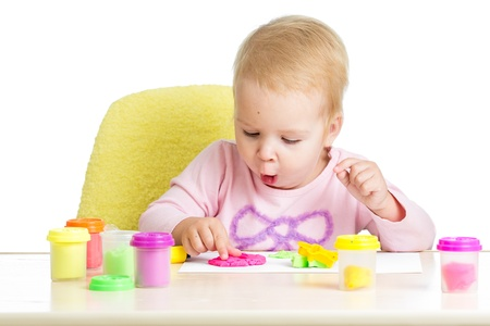 little dough: Little kid sitting at table playing with colorful clay