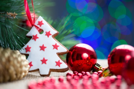Christmas tree with bauble and cake over bright festive background photo