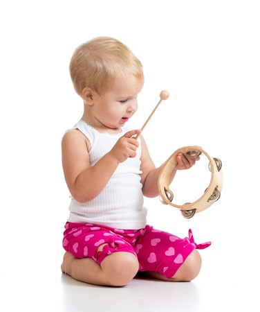 tambourine: Child playing with musical toy  Isolated on white background