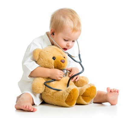 sick teddy bear: Adorable girl with clothes of doctor isolated on white Stock Photo