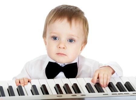 tocando piano: adorable niño tocando el piano electrónico Foto de archivo
