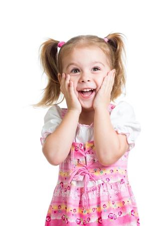ni�as peque�as: chica ni�o divertido con las manos cerca de la cara aislada en el fondo blanco Foto de archivo