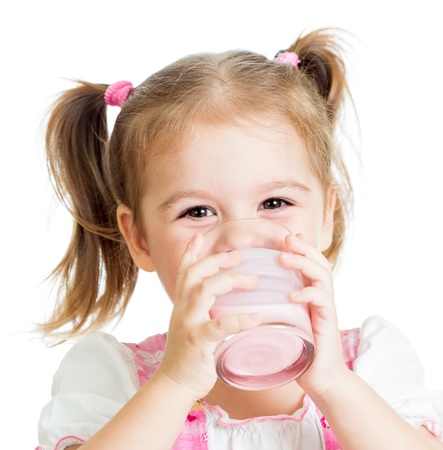 kefir: little child girl drinking yogurt or kefir over white