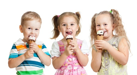 face cream: happy children boy and girls eating ice cream in studio isolated Stock Photo