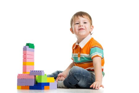 toddler playing: cheerful child boy with construction set over white background