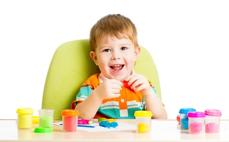 clay craft: Happy little kid sitting at table and playing with colorful clay toy