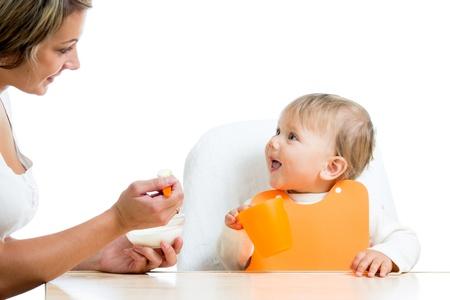 baby feeding: mother spoon feeding her baby girl