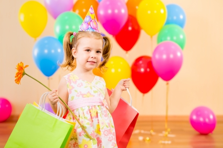pretty child girl with gifts and flower on birthday party photo