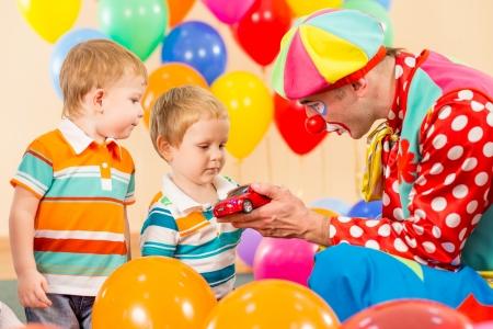 clown making present child boy on birthday party photo