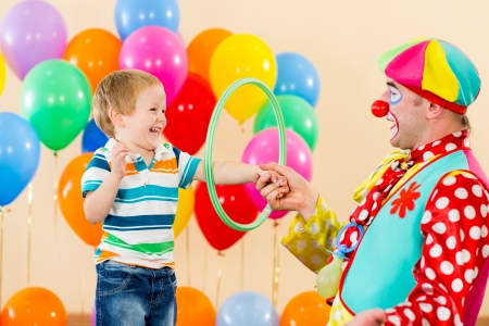 clown amusing kid boy on birthday party photo