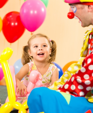 happy child girl and clown playing on birthday party photo