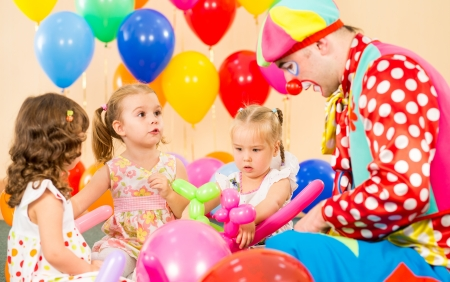 children girls and clown on birthday party photo