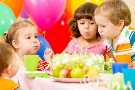 birthday food: kids celebrating birthday party and blowing candles on cake