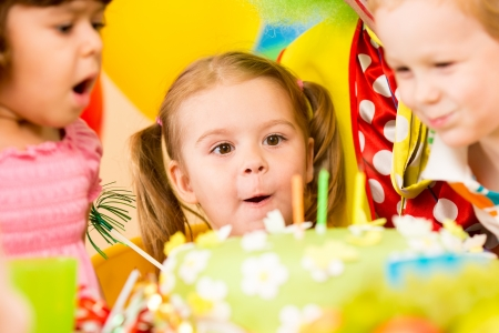 birthday party kids: funny kids celebrating birthday party and blowing candles on cake