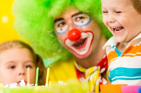 kids with clown celebrating birthday party and blowing candles on cake photo