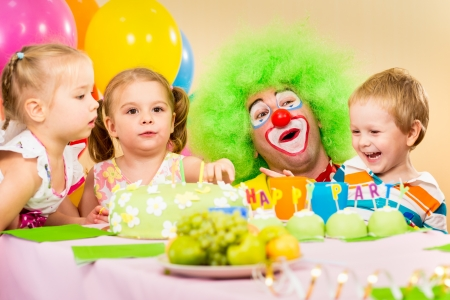 kids celebrating birthday party with clown photo