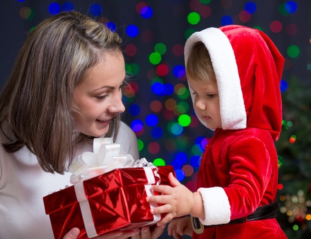 baby girl and her mother holding gift box on bright festive background Stock Photo - 16143354