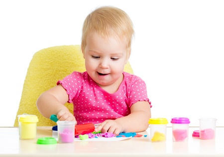 Little kid sitting at table playing with colorful clay photo