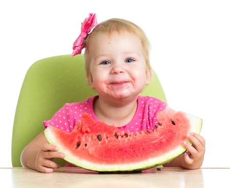 Little girl eating watermelon at table Stock Photo - 16143373