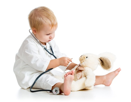 Adorable child dressed as doctor playing with toy over white
